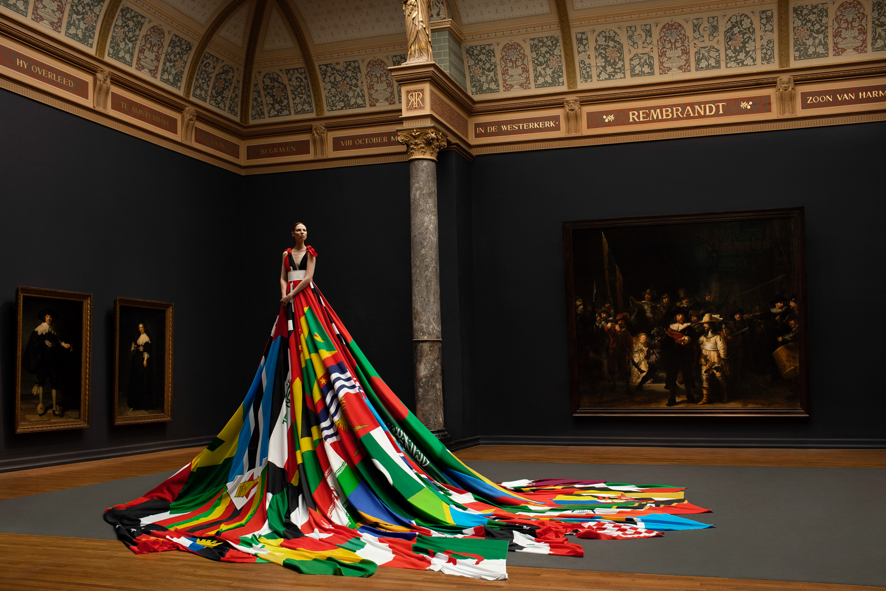 Valentijn de Hingh presents the Amsterdam Rainbow Dress in the Gallery of Honour at the Rijksmuseum Amsterdam, in front of Rembrandt's iconic Night Watch. Image by Pieter Henket Studio.