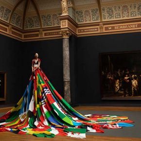 Valentijn de Hingh presents the Amsterdam Rainbow Dress in the Gallery of Honour at the Rijksmuseum, in front of Rembrandt's iconic Night Watch. Image by Pieter Henket Studio.